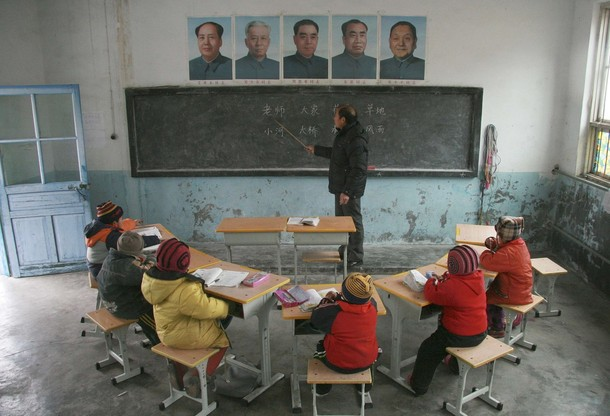 Pupils listen to the teacher under the portraits of China's former leaders at Gao'er Hope School located on the top of Xiaohuatan Mountain in Jinan